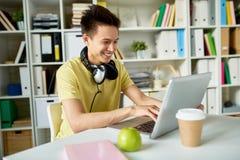 Счастливый азиатский студент используя компьтер-книжку стоковое фото