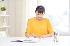 Счастливый азиатский студент молодой женщины уча дома Стоковое Фото