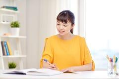 Счастливый азиатский студент молодой женщины уча дома Стоковые Фотографии RF