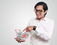 Счастливый азиатский человек с вагонеткой покупок Стоковое фото RF