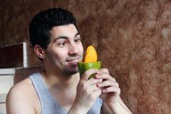 Счастливый арабский молодой человек есть плодоовощ манго Стоковая Фотография