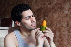 Счастливый арабский молодой человек есть плодоовощ манго Стоковые Изображения