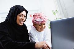 Счастливый арабский ребенок дома с его матерью Стоковые Изображения