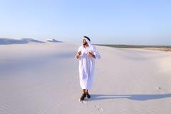 Счастливый арабский человек идет в середину белой пустыни и наслаждается жизнью o Стоковые Изображения RF
