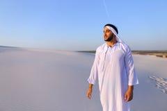 Счастливый арабский человек идет в середину белой пустыни и наслаждается жизнью o Стоковые Фотографии RF