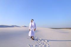Счастливый арабский человек идет в середину белой пустыни и наслаждается жизнью o Стоковое Изображение RF