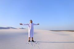 Счастливый арабский человек идет в середину белой пустыни и наслаждается жизнью o Стоковое фото RF
