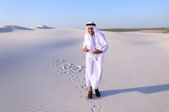 Счастливый арабский человек идет в середину белой пустыни и наслаждается жизнью o Стоковая Фотография RF