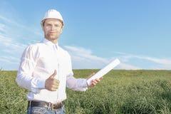 Счастливый архитектор инженера в белом шлеме при светокопии держа его большой палец руки поднимающий вверх и усмехаться Стоковые Фотографии RF