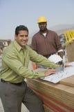 Счастливый архитектор работая на компьтер-книжке на месте Стоковые Фотографии RF