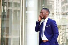 Счастливый африканский бизнесмен говоря на сотовом телефоне Стоковые Фотографии RF