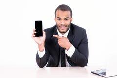 Счастливый африканский бизнесмен сидя на таблице и указывая на a Стоковое Изображение