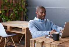 Счастливый африканский предприниматель работая на компьтер-книжке в офисе Стоковые Изображения
