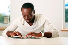 счастливый африканский человек сидя на таблице Стоковые Фото