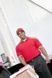 Счастливый Афро-американский работник доставляющий покупки на дом нажимая handtruck Стоковое Изображение RF