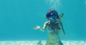 Счастливый белокурый скакать в шноркель бассейна нося и держать морские звёзды акции видеоматериалы