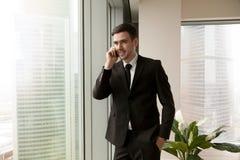 Счастливый бизнесмен говоря на клетке стоя около большого windo офиса Стоковое Фото