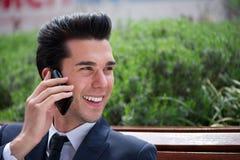 Счастливый бизнесмен говоря на телефоне вне офиса Стоковые Фото