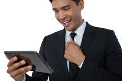 Счастливый бизнесмен держа галстук пока использующ планшет стоковые изображения