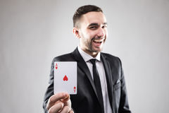 Счастливый бизнесмен держа карточку туза Стоковая Фотография