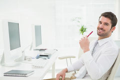 Счастливый бизнесмен используя его компьютер стоковые изображения