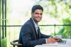 Счастливый бизнесмен используя компьтер-книжку в ресторане Стоковые Фото