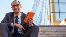 Счастливый бизнесмен используя ПК таблетки в оранжевой крышке на str города Стоковые Изображения