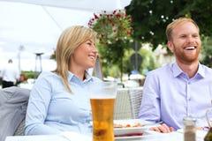 Счастливый бизнесмен и коммерсантка сидя на внешнем ресторане Стоковое Фото