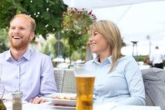 Счастливый бизнесмен и коммерсантка сидя на внешнем ресторане Стоковые Изображения