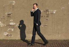 Счастливый бизнесмен идя и говоря на мобильном телефоне Стоковое фото RF