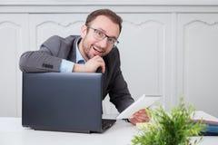 Счастливый бизнесмен на столе офиса стоковая фотография
