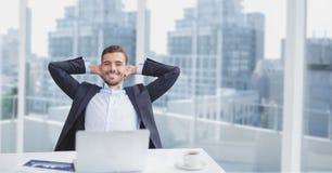 Счастливый бизнесмен на столе сидя против предпосылки города стоковая фотография