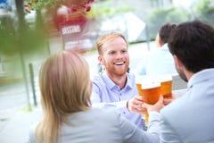 Счастливый бизнесмен провозглашать стекло пива с коллегами на внешнем ресторане Стоковые Изображения RF