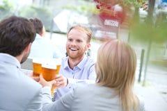 Счастливый бизнесмен провозглашать стекло пива с коллегами на внешнем ресторане Стоковое Изображение RF