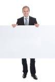 Счастливый бизнесмен проводя пустой плакат Стоковое фото RF