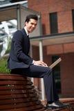 Счастливый бизнесмен работая на компьтер-книжке вне офиса Стоковые Фотографии RF