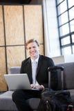 Счастливый бизнесмен сидя на софе и используя компьтер-книжку Стоковая Фотография RF