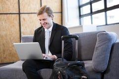 Счастливый бизнесмен сидя на софе и используя компьтер-книжку Стоковые Изображения