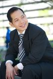 Счастливый бизнесмен сидя outdoors стоковая фотография rf