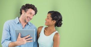 Счастливый бизнесмен смотря женского коллеги пока держащ цифровую таблетку против зеленой предпосылки Стоковое Изображение RF