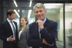 Счастливый бизнесмен стоя в офисе Стоковая Фотография