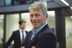Счастливый бизнесмен стоя в офисе Стоковое Фото