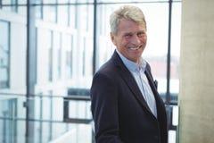 Счастливый бизнесмен стоя в офисе Стоковые Изображения