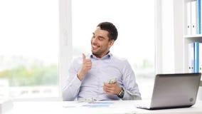 Счастливый бизнесмен с деньгами и компьтер-книжкой в офисе акции видеоматериалы