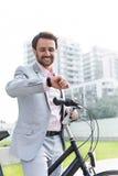 Счастливый бизнесмен с контрольным временем велосипеда outdoors Стоковые Фото