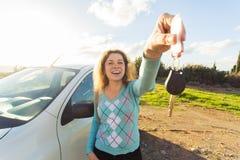 Счастливый водитель женщины показывая ключи автомобиля на предпосылке ее автомобиля Стоковая Фотография RF