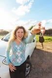 Счастливый водитель женщины показывая ключи автомобиля на предпосылке ее автомобиля Стоковое Изображение