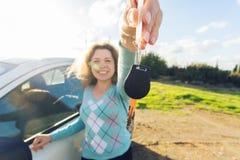 Счастливый водитель женщины показывая ключи автомобиля на предпосылке ее автомобиля Стоковое фото RF
