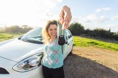 Счастливый водитель женщины показывая ключи автомобиля на предпосылке ее автомобиля Стоковое Изображение RF