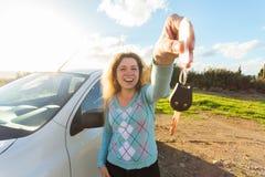 Счастливый водитель женщины показывая ключи автомобиля на предпосылке ее автомобиля Стоковые Изображения RF